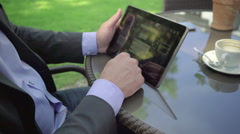 Close up on businessman's hand browsing tablet. Outdoor. Steadicam shot. Stock Footage