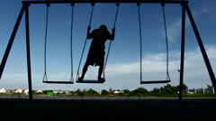 Silhouette boy playing swing alone Stock Footage