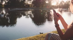 Woman Relaxes by Sunny Lake Taking Picture on Smartphone. SLOW MOTION 120 fps 4K - stock footage