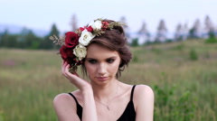 Beautiful girl in the black short dress with the wreath on her head on the green - stock footage