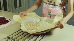 Cooking a pie. A woman removing the grains from form for baking. Slow motion. HD - stock footage
