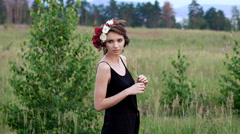 Beautiful girl in the black short dress with the wreath on her head on the green Stock Footage
