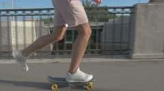 Legs of skateboarder to ride a skateboard on the road in the city Stock Footage