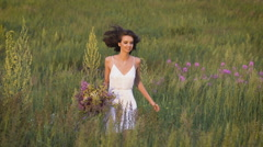 One young woman running on green field with flower bunch and smiling Stock Footage