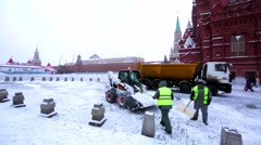 Workers and snowplow clean pedestrian area near Moscow Kremlin and Red Square Stock Footage