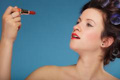 Girl in hair curlers applying red lipstick - stock photo