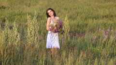 One young woman walking on green field with flower bunch and smiling Stock Footage