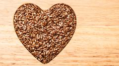 Raw flax seeds linseed heart shaped Stock Photos