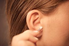 Woman cleaning ear with cotton swabs closeup Stock Photos