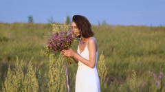 One young woman standing on green field smelling flower bunch Stock Footage