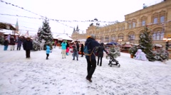 View of walking people in the Christmas fair on the Red Square, and carrousels Stock Footage