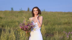 One young woman standing on green field with flower bunch and smiling Stock Footage