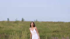 One young woman standing on green field throwing a flower bunch Stock Footage