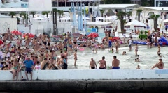 Waterfront resort. People sunbathing on the beach and swimming in the sea Stock Footage