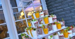 mini canapes in plastic cups decorated with edible flowers - stock footage