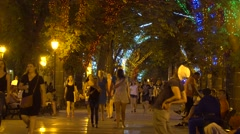 People walk on the festively decorated streets. Evening time Stock Footage