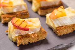 Canapes, Appetizer with grilled brie Stock Photos
