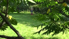 gardener man with flip-flop shoes mow lawn. View through trees. 4K - stock footage