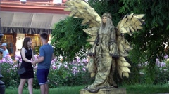 Woman mime with wings on the street. Near is a young couple in love. Stock Footage