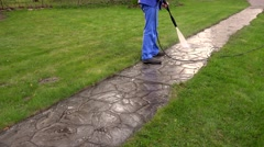 Man Washing Concrete Path With Pressure Washer - stock footage