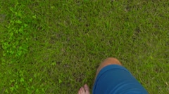 Man walking barefoot on the grass in apple garden, POV. 4K shot Stock Footage