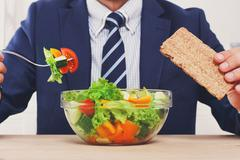 Unrecognizable man has healthy business lunch in modern office - stock photo