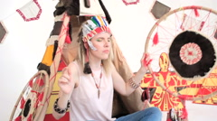 Model with tambourine dancing while sitting at wigwam Stock Footage