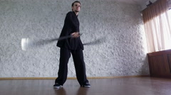 Man practicing elements of tai chi. A man rotating steel swords around a body 4K - stock footage