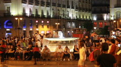 People around the fountain on Puerta del Sol, Madrid in the evening Stock Footage