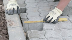 Measuring pavement before cutting pavement stone Stock Footage