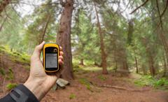 Finding the right position in the forest via gps ( blurred background ) Stock Photos