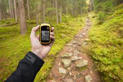 A trekker is finding the right position in the forest via gps in a cloudy aut - stock photo