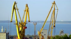 Cranes in seaport You can see the harbor and the city on the horizon - stock footage