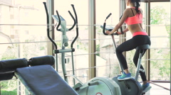 Sexy girl doing exercise with exercise bike in the gym. Look behind her - stock footage