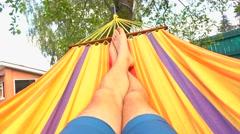 Barefooted man swinging in hammock 4K video Stock Footage