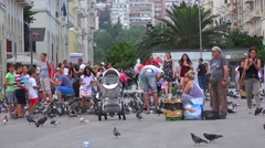 Children feed pigeons and chase them at the Aristotelous Square. Stock Footage
