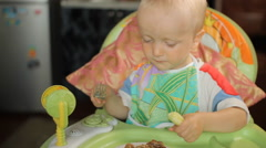 Beautiful blond baby boy sitting at a table and eating hamburger Stock Footage