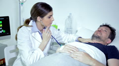 Female doctor listening heart beat of sick male patient in hospital Stock Footage