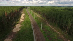 Drone flying over empty double line railway in coniferous woods of Karelia, Rus Stock Footage