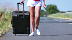 Slow motion. Hot summer day and   woman  slender legs with  suitcase on  road. Stock Footage