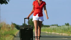 Slow motion. Sexy woman  slender legs and body in red blouse go on road Stock Footage