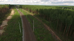 Freight train coming at the double line railway with electric poles in woods Stock Footage