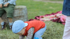 Boy playing with other children and hay. He picks up and throws hay to another - stock footage