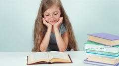 Close up portrait happy schoolgirl 7-8 years old reading book on the table - stock footage