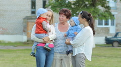 2 mothers with children and a grandmother talking to each other. Everyone laughs Stock Footage