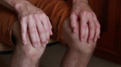 Man sits and rubs knees Stock Footage