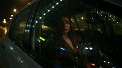 Beautiful brunette girl behind car window at rainy night Arkistovideo