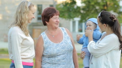 2 mothers with children and a grandmother talking to each other. Everyone laughs - stock footage