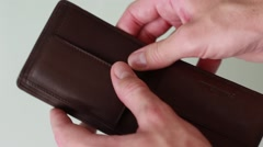 Looking for money in an empty purse Stock Footage