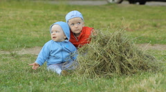 2 boys to play with each other and hay. One less than a year, another two years - stock footage